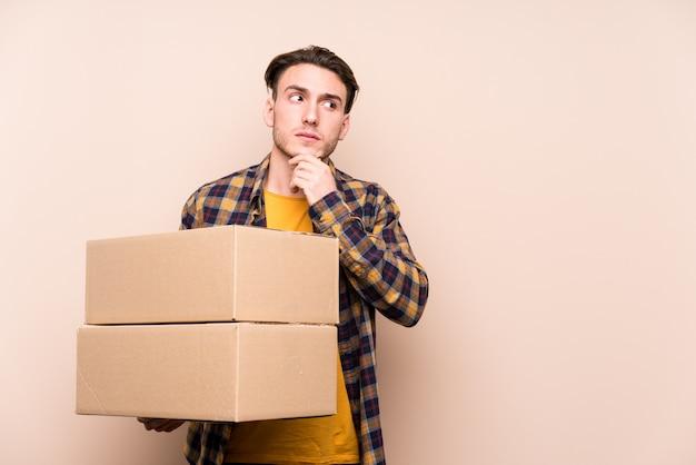 Jeune homme caucasien tenant des boîtes à la recherche sur le côté avec une expression douteuse et sceptique.