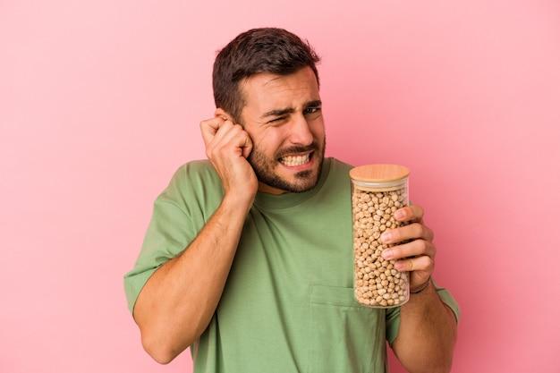 Jeune homme caucasien tenant une bouteille de pois chiche isolée sur un mur rose couvrant les oreilles avec les mains