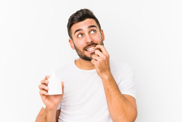 Jeune homme caucasien tenant une bouteille de vitamines isolée pensée détendue sur quelque chose en regardant un espace de copie.