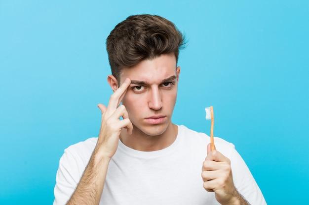 Jeune homme caucasien tenant une brosse à dents jeune femme indienne portant un pyjama et un masque de sommeil isolé tenant un oreiller pointant sa tempe avec le doigt, pensant, concentrée sur une tâche. <mixto>