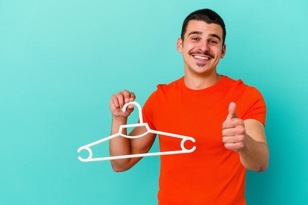 Jeune homme caucasien tenant un cintre sur bleu souriant et levant le pouce vers le haut