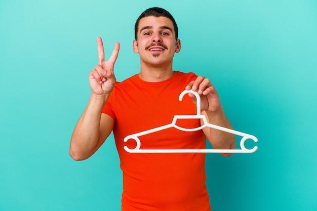 Jeune homme caucasien tenant un cintre isolé sur fond bleu montrant le numéro deux avec les doigts.
