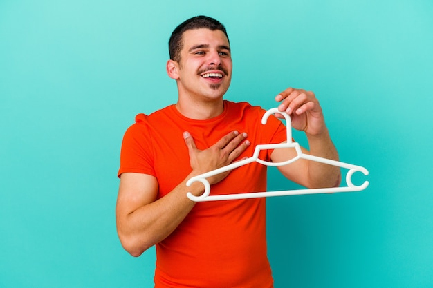 Jeune homme caucasien tenant un cintre isolé sur un mur bleu éclate de rire en gardant la main sur la poitrine.