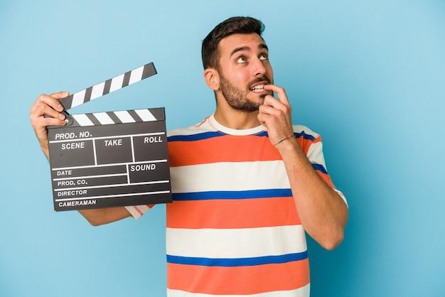 Jeune homme caucasien tenant un clap isolé sur fond bleu pensée détendue sur quelque chose en regardant un.