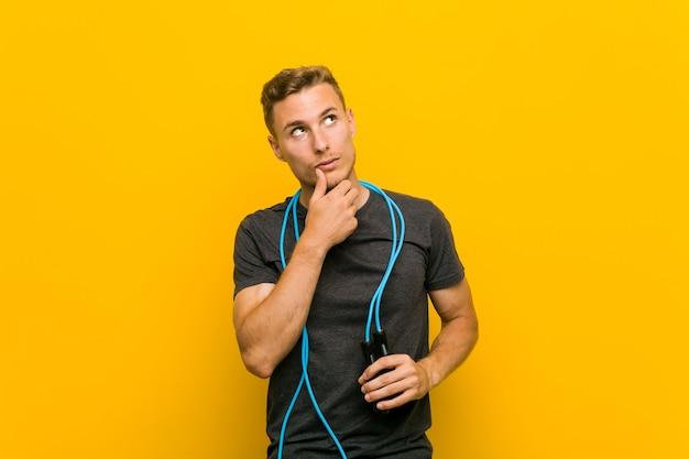 Jeune homme caucasien tenant une corde à sauter à la recherche sur le côté avec une expression douteuse et sceptique.