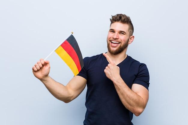 Jeune homme caucasien tenant un drapeau de l'allemagne souriant joyeusement pointant avec l'index loin.
