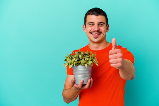 Jeune homme caucasien tenant une feuille isolée sur un mur bleu souriant et levant le pouce vers le haut