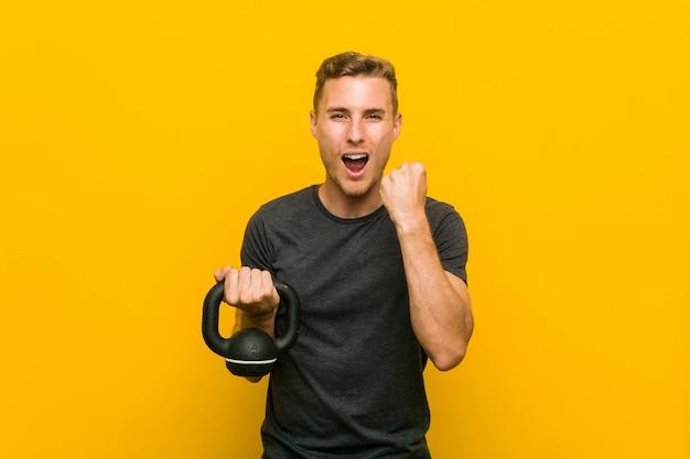 Jeune homme caucasien tenant un haltère applaudissant insouciant et excité