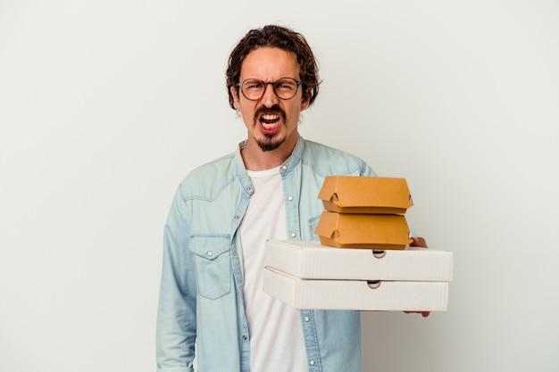 Jeune homme caucasien tenant un hamburger une pizzas isolé sur fond blanc criant très en colère et agressif.