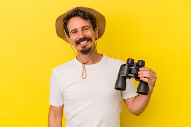 Jeune homme caucasien tenant des jumelles isolées sur fond jaune heureux, souriant et joyeux.