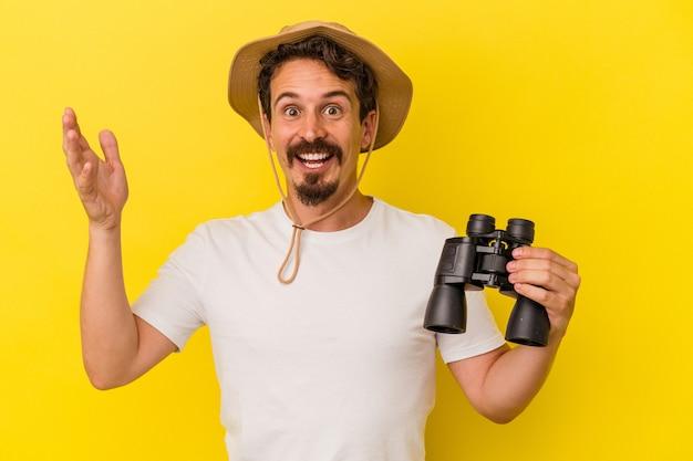 Jeune homme caucasien tenant des jumelles isolées sur fond jaune recevant une agréable surprise, excité et levant les mains.