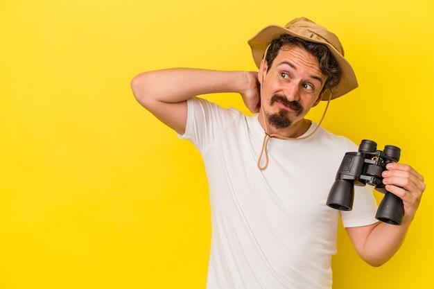 Jeune homme caucasien tenant des jumelles isolées sur fond jaune touchant l'arrière de la tête, pensant et faisant un choix.