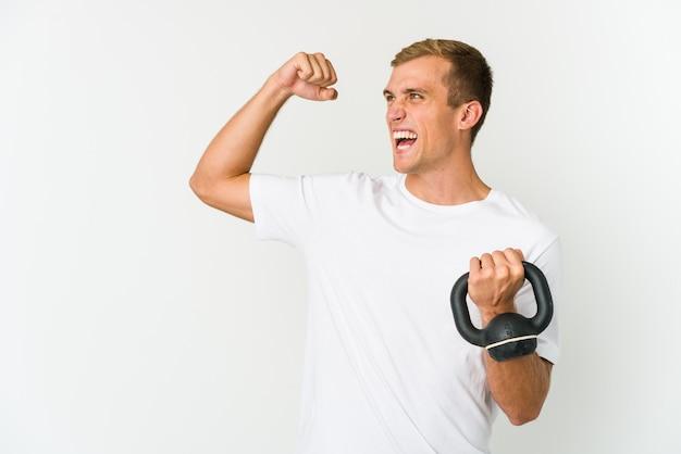 Jeune homme caucasien tenant un kettlebell isolé sur fond blanc levant le poing après une victoire, concept gagnant.