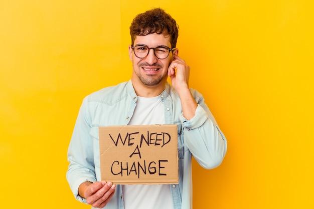 Jeune homme caucasien tenant un nous avons besoin d'une plaque-étiquette de changement isolé couvrant les oreilles avec les mains.