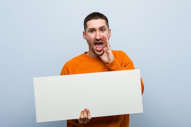 Jeune homme caucasien tenant une pancarte criant excité à l'avant.