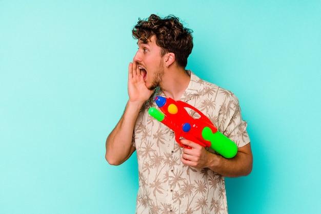 Jeune homme caucasien tenant un pistolet à eau isolé sur fond bleu criant et tenant la paume près de la bouche ouverte.