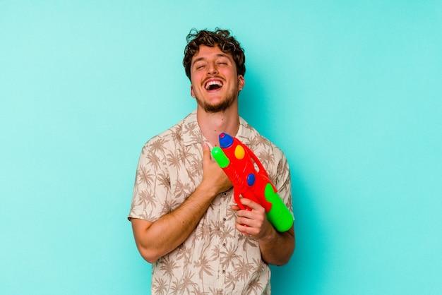 Jeune homme caucasien tenant un pistolet à eau isolé sur fond bleu éclate de rire en gardant la main sur la poitrine.