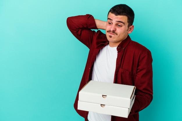 Jeune homme caucasien tenant des pizzas sur le bleu touchant l'arrière de la tête, en pensant et en faisant un choix.