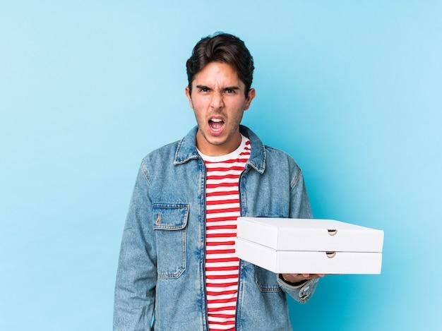 Jeune homme caucasien tenant des pizzas isolées criant très en colère et agressif.