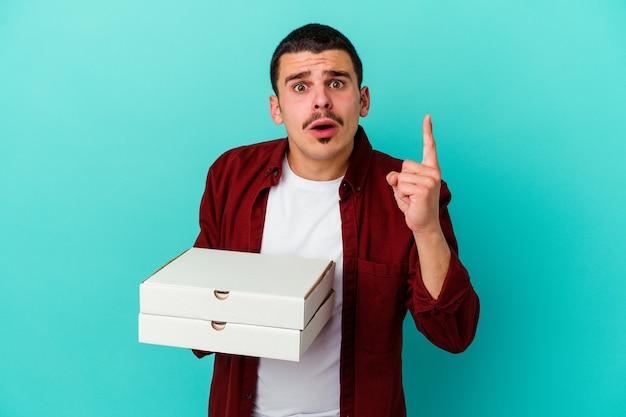 Jeune homme caucasien tenant des pizzas isolées sur fond bleu ayant une idée, concept d'inspiration.