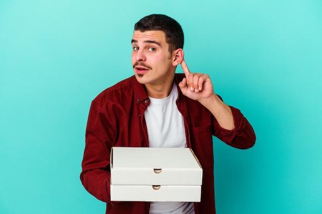 Jeune homme caucasien tenant des pizzas isolées sur fond bleu essayant d'écouter un potin.