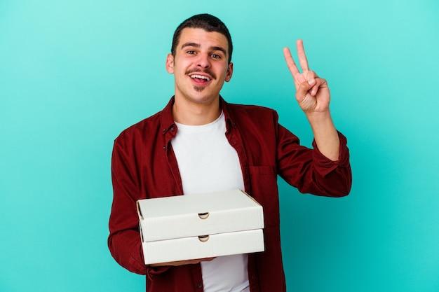 Jeune homme caucasien tenant des pizzas isolées sur fond bleu joyeux et insouciant montrant un symbole de paix avec les doigts.