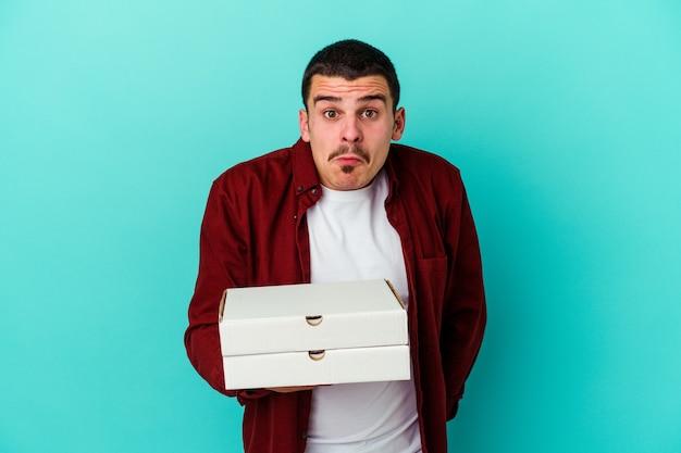 Jeune homme caucasien tenant des pizzas isolées sur le mur bleu hausse les épaules et les yeux ouverts confus.