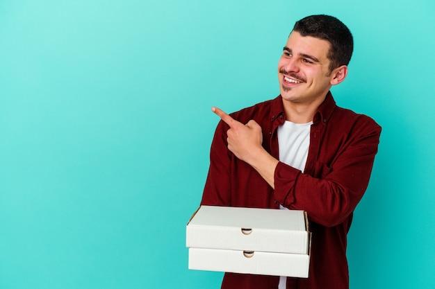 Jeune homme caucasien tenant des pizzas isolées sur un mur bleu souriant et pointant de côté, montrant quelque chose à l'espace vide.