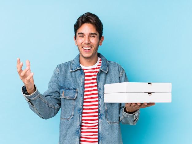 Jeune homme caucasien tenant des pizzas isolées recevant une agréable surprise, excité et levant les mains.