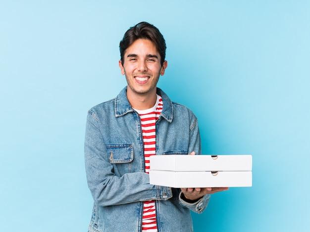 Jeune homme caucasien tenant des pizzas isolées en riant et en s'amusant.