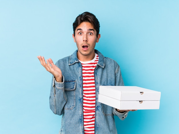 Jeune homme caucasien tenant des pizzas isolées surpris et choqué.