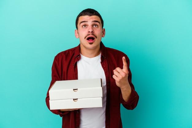 Jeune homme caucasien tenant des pizzas isolés sur un mur bleu pointant vers le haut avec la bouche ouverte.