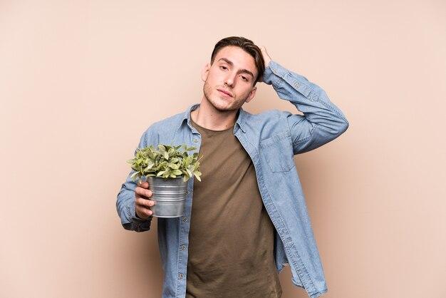 Jeune homme caucasien tenant une plante choquée, elle s'est souvenue d'une réunion importante.
