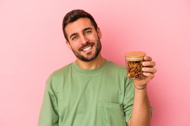 Jeune homme caucasien tenant un pot d'amande isolé sur un mur rose heureux, souriant et joyeux.