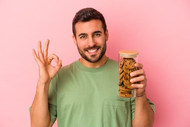 Jeune homme caucasien tenant le pot de biscuits isolé sur fond rose joyeux et confiant montrant le geste ok.