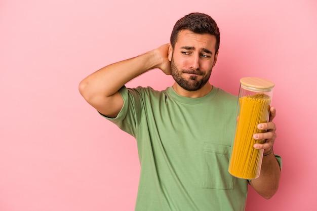 Jeune homme caucasien tenant un pot de pâtes isolé sur un mur rose touchant l'arrière de la tête, en pensant et en faisant un choix