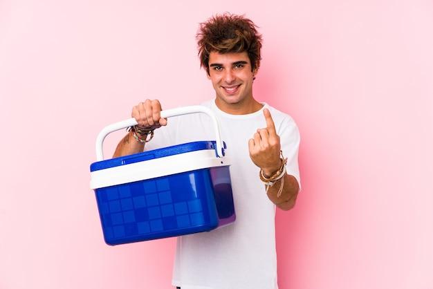 Jeune homme caucasien tenant un réfrigérateur portable pointant avec le doigt sur vous comme si vous invitiez à vous rapprocher.