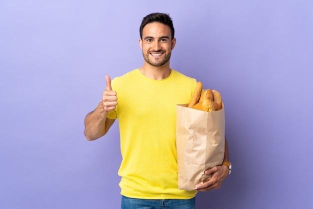 Jeune homme caucasien tenant un sac plein de pains isolé sur mur violet donnant un geste de pouce en l'air