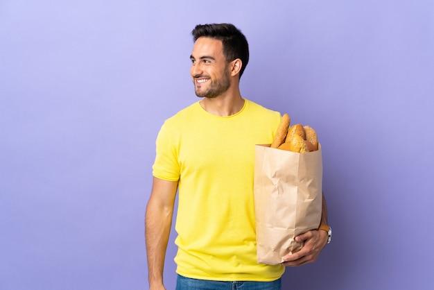 Jeune homme caucasien tenant un sac plein de pains isolé sur mur violet en riant