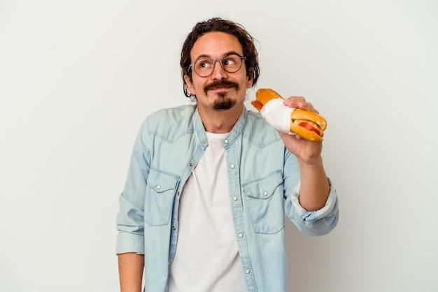 Jeune homme caucasien tenant un sandwich isolé sur blanc rêvant d'atteindre les objectifs et les buts