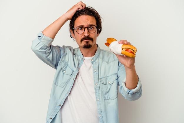 Jeune homme caucasien tenant un sandwich isolé sur fond blanc étant choqué, elle s'est souvenue d'une réunion importante.