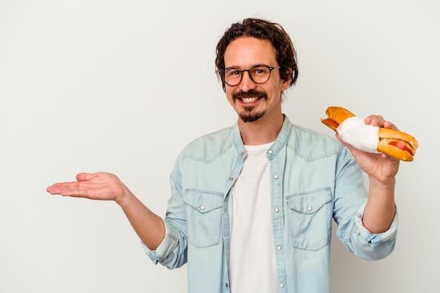 Jeune homme caucasien tenant un sandwich isolé sur fond blanc montrant un espace de copie sur une paume et tenant une autre main sur la taille.