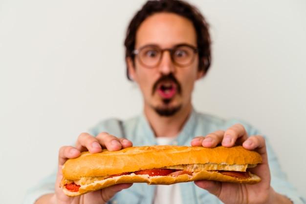 Jeune homme caucasien tenant un sandwich isolé sur fond blanc