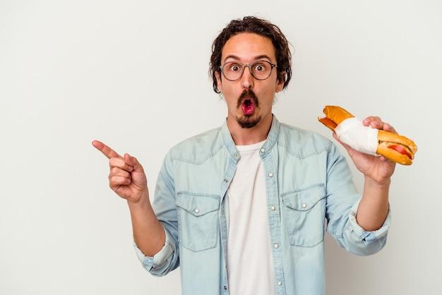 Jeune homme caucasien tenant un sandwich isolé sur un mur blanc pointant vers le côté