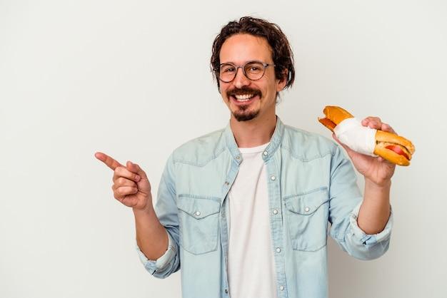 Jeune homme caucasien tenant un sandwich isolé sur un mur blanc souriant et pointant de côté, montrant quelque chose à l'espace vide.