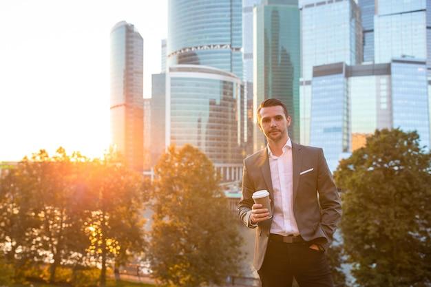 Jeune homme caucasien tenant le smartphone pour le travail en entreprise.