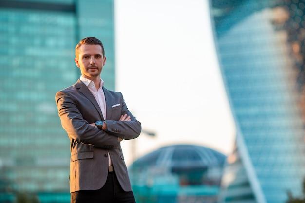 Jeune homme caucasien tenant le smartphone pour le travail d'entreprise.