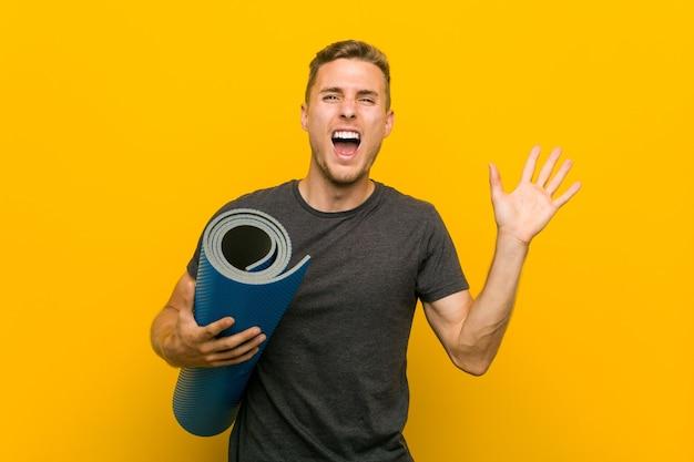 Jeune homme caucasien tenant un tapis célébrant une victoire ou un succès