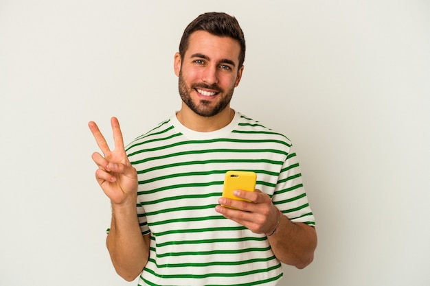Jeune homme caucasien tenant un téléphone mobile isolé sur fond blanc montrant le numéro deux avec les doigts.