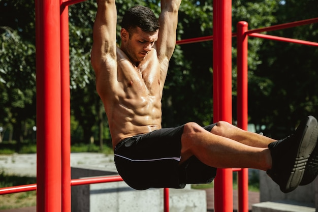 Jeune homme caucasien torse nu musclé faisant des tractions sur la barre horizontale au terrain de jeux en journée d'été ensoleillée. entraîner le haut de son corps à l'extérieur. concept de sport, entraînement, mode de vie sain, bien-être.